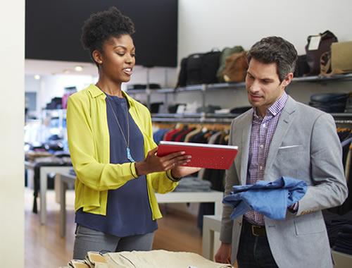 Duas pessoas em uma loja de departamentos olhando para um tablet