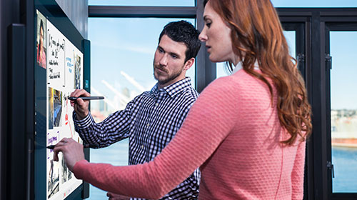 Two people working at a Microsoft Surface Hub.