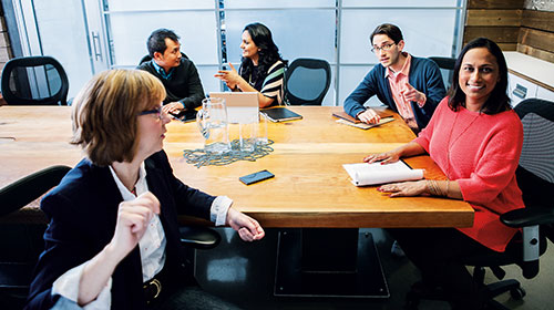 Group of people sitting at a conference table.