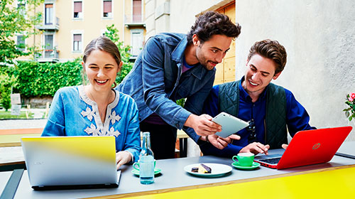 Three people working at laptops and tablets outside.