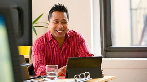 Man sitting at a desk behind a computer.