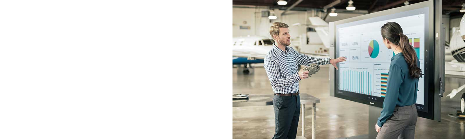 Man and woman working on Surface Hub in airplane hangar